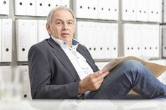 Mature man sitting in front of a shelf wall with documents folder Stock Photo