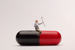 Mature man sitting on a giant pill. And holding a walking cane royalty free stock photography
