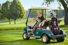 Mature man sitting in a golfcart. On the green Stock Photo