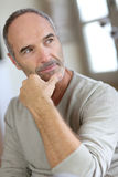 Mature man sitting with hand under chin Royalty Free Stock Photography