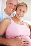 Mature man sitting with his pretty pregnant wife Royalty Free Stock Photo