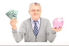 Mature man sitting, holding money and a piggy bank Stock Photo