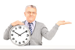 Mature man sitting and holding a wall clock Royalty Free Stock Photography