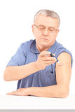 Mature man sitting and injecting insulin in his arm. On white background royalty free stock image
