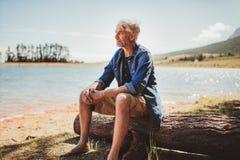 Mature man sitting on a log near lake Stock Photography