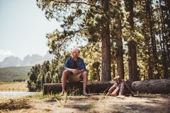 Mature man sitting on a log near lake Stock Images
