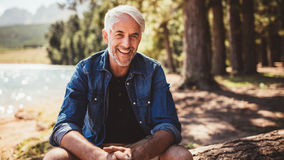 Mature man sitting on a log near lake. Portrait of a mature man sitting on a log near the lake. Senior caucasian man sitting alone on the lake and looking at a Royalty Free Stock Photo