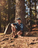 Mature man sitting on a log near lake Royalty Free Stock Photography