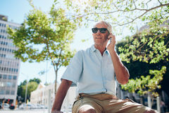 Mature man sitting outdoors in the city making a phone call Royalty Free Stock Images