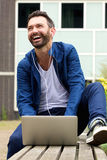 Mature man sitting outdoors with laptop and laughing. Portrait of mature man sitting outdoors with laptop looking away and laughing royalty free stock photos