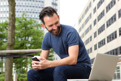 Mature man sitting outdoors looking at laptop. Portrait of mature man sitting outdoors with mobile phone looking at laptop and smiling Stock Photos