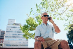 Mature man sitting outdoors talking on cell phone Stock Images