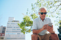 Mature man sitting outdoors using mobile phone Royalty Free Stock Photo