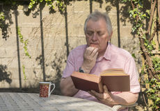 Mature man sitting outside reading a book Stock Photography