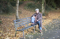 Mature man sitting on a park bench Stock Photo