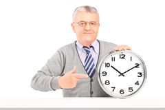 Mature man sitting and pointing on a wall clock Royalty Free Stock Photo