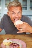 Mature Man Sitting At Table Eating Sugary Donut Stock Photo