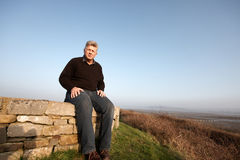 A mature man sitting on a wall Royalty Free Stock Image