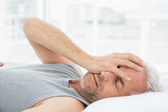 Mature man sleeping in bed. Closeup of a mature man sleeping in bed at home Royalty Free Stock Images