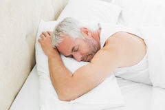 Mature man sleeping in bed. High angle view of a mature man sleeping in bed at home Stock Photography