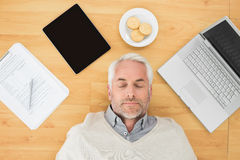 Mature man sleeping with electronics and biscuits on parquet floor. Overhead view of a mature man sleeping with electronics and biscuits on parquet floor at home Royalty Free Stock Photo