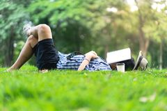 Mature man sleeping on green grass in city park with a book cov royalty free stock image