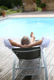 Mature man sleeping near pool. Back view of senior man reaxing in long chair Stock Image