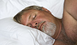 Mature man sleeping peacefully. Senior man sleeping peacefully - intentional low light and shallow depth of field Stock Image