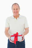 Mature man smiling at camera holding gift Stock Photography