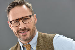 Mature man smiling isolated. Mature man with eyeglasses standing on grey background royalty free stock image