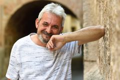 Mature man smiling looking at camera in urban background. Mature man smiling at camera in urban background. Senior male with white hair and beard wearing casual royalty free stock photography