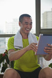 Mature man smiling and looking at his digital tablet after working out at the gym Royalty Free Stock Photo
