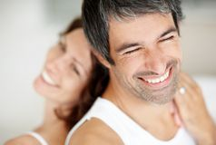 Mature man smiling with wife relaxing on his back Stock Photos