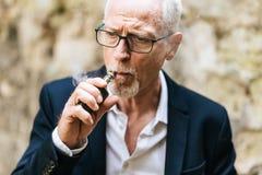 Mature man smoking electronic cigarette. Portrait of mature man smoking electronic cigarette royalty free stock photography