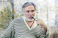 Mature man smoking tobacco pipe Royalty Free Stock Photo