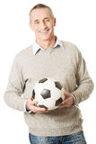 Mature man with a soccer ball Royalty Free Stock Photos
