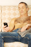 Mature man on a sofa looking at his smartphone Stock Photography