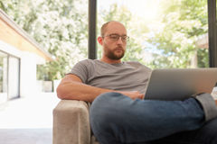 Mature man on a sofa using laptop Stock Images