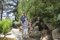 Mature man with son fishing at lake Stock Images