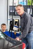 Mature man with son refueling vehicle with gas Royalty Free Stock Images