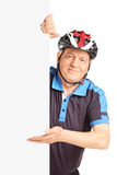 Mature man with sports helmet pointing on a billboard Royalty Free Stock Photography