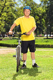 Mature man in sportswear posing next to his bike in a park Royalty Free Stock Photo