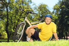 Mature man in sportswear sitting on a green glass with his bicyc Stock Image