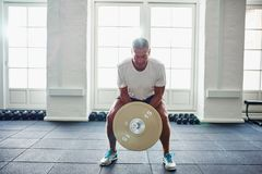 Mature man straining while lifting weights at a gym stock photography