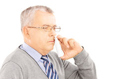 Mature man spraying nose drops. Isolated on white background stock photo