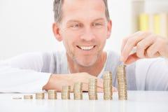 Mature man stacking coins Stock Image