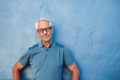 Mature man standing against a blue wall Stock Photos