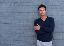 Mature man standing against gray wall with arms crossed Royalty Free Stock Photography