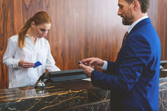 Mature man standing at check-in desk Royalty Free Stock Image