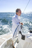Mature man standing at helm of yacht out at sea, steering, smiling, side view Stock Images